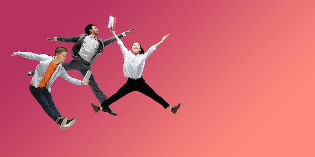 Szczęśliwi pracownicy biurowi skaczą i tańczą w zwykłych ubraniach lub garniturze na płynnym tle gradientu neonu. ulotka z copyspace