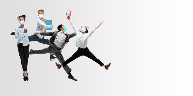Szczęśliwi pracownicy biurowi w maskach na twarz skaczą i tańczą w zwykłych ubraniach lub garniturach na białym tle