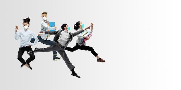 Szczęśliwi pracownicy biurowi w maskach na twarz skaczą i tańczą w zwykłych ubraniach