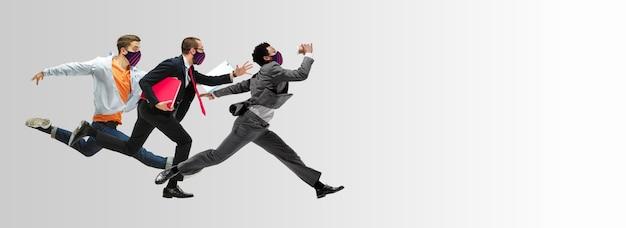Szczęśliwi pracownicy biurowi w maskach na twarz, skacząc i tańcząc w ubraniu lub garniturze na białym tle na tle studia. koncepcja biznesowa, start-up, profilaktyka covid, motion and action. kreatywny kolaż.
