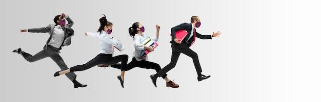 Szczęśliwi pracownicy biurowi w maskach na twarz skaczący i tańczący w zwykłych ubraniach lub garniturze na białym tle w studio