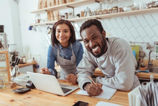 Szczęśliwi pracownicy. pogodni młodzi bariści stoją za ladą kawiarni i uśmiechają się do kamery, tworząc nowe menu dla tego miejsca