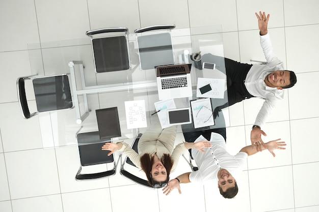 Szczęśliwi pracownicy siedzący przy biurku.