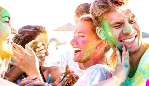 Szczęśliwi przyjaciele bawią się na imprezie na plaży na festiwalu kolorów holi