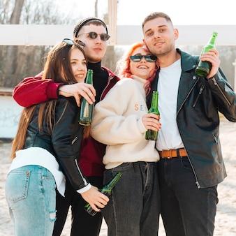 Szczęśliwi przyjaciele bawią się razem i piją piwo na świeżym powietrzu