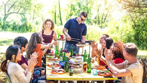 Szczęśliwi przyjaciele bawią się razem na pikniku przy grillu
