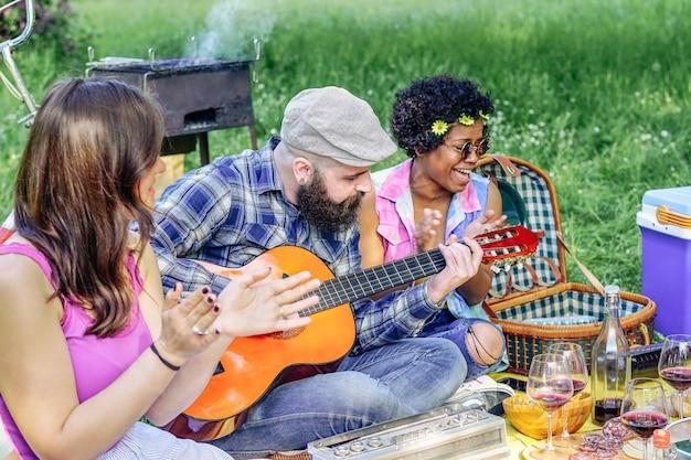 Szczęśliwi przyjaciele bawić się gitarę przy pyknicznym lunchem w parku plenerowym