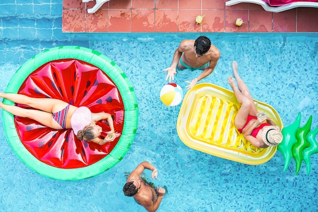 Szczęśliwi przyjaciele bawić się z lotniczą lilo piłką wśrodku pływackiego basenu