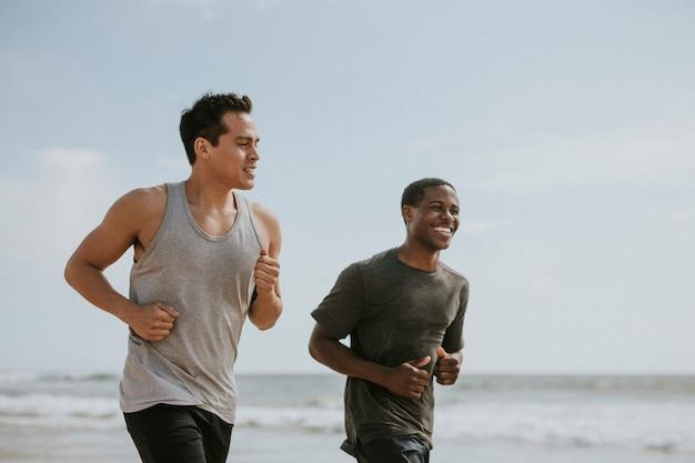 Szczęśliwi przyjaciele biegający razem na plaży