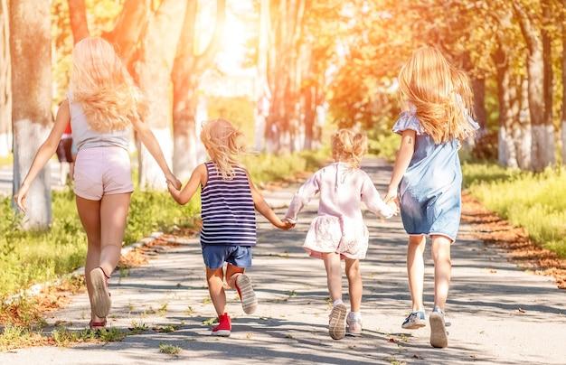 Szczęśliwi przyjaciele biegnący wzdłuż letniej drogi parkowej