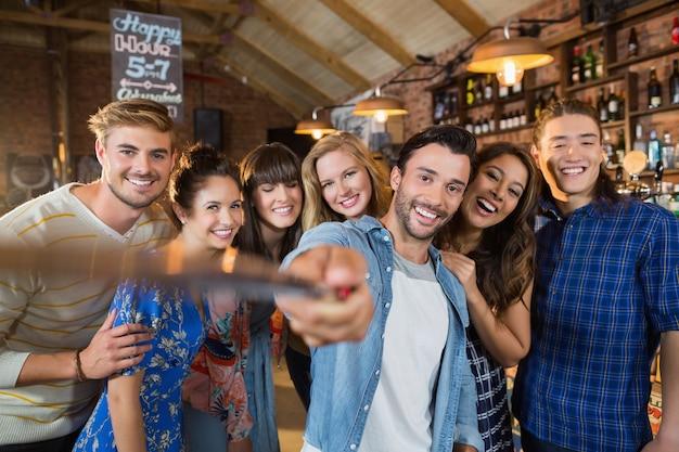 Szczęśliwi przyjaciele biorąc selfie w pubie