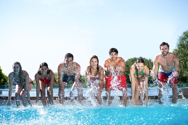 Szczęśliwi przyjaciele ciesząc się w basenie