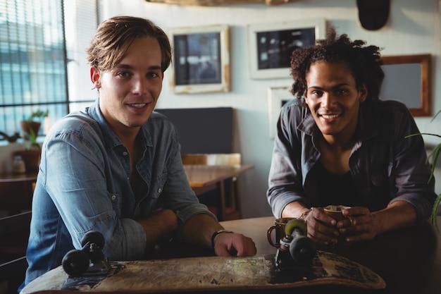 Szczęśliwi przyjaciele cieszy się kawę przy restauracją