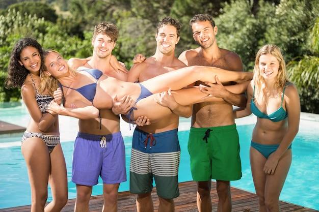 Szczęśliwi przyjaciele cieszy się w pływackim basenie