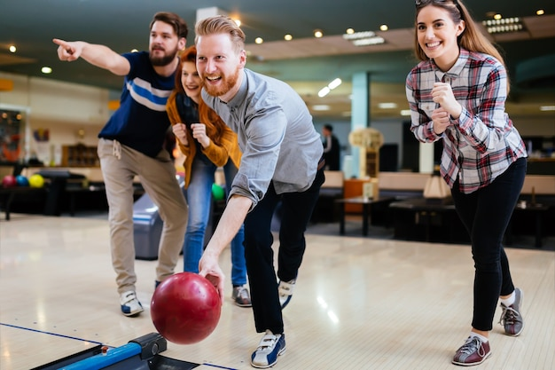Szczęśliwi przyjaciele dobrze się bawią i cieszą się wspólną grą w kręgle