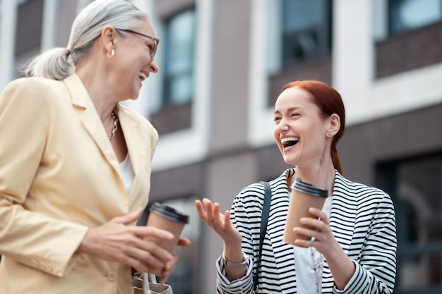 Szczęśliwi przyjaciele. dwoje szczęśliwych kaukaskich przyjaciół w stylowych kurtkach spędzających wolny czas po pracy