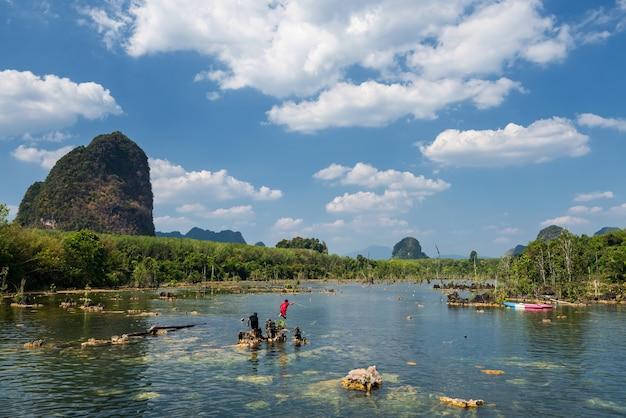 Szczęśliwi przyjaciele dzieci skaczą i bawią się na jeziorze z błękitnym niebem i wapienną górą w klong rood, krabi, tajlandia.