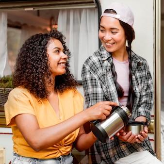 Szczęśliwi przyjaciele dzielą się gorącą kawą