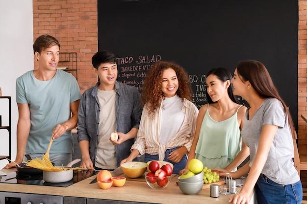 Szczęśliwi przyjaciele gotują razem w kuchni
