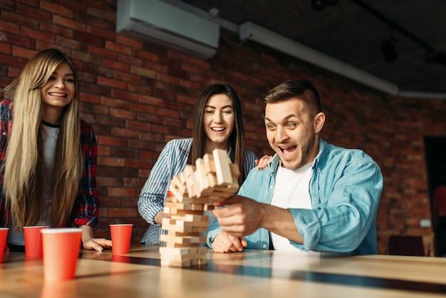 Szczęśliwi przyjaciele grają jengę przy stole w kawiarni