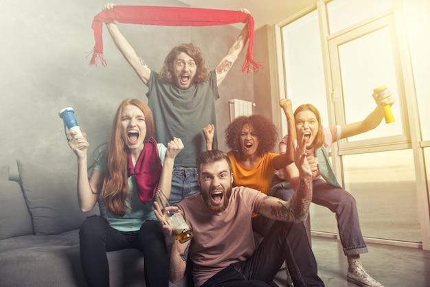 Szczęśliwi przyjaciele kibiców oglądających piłkę nożną w telewizji i świętujących zwycięstwo
