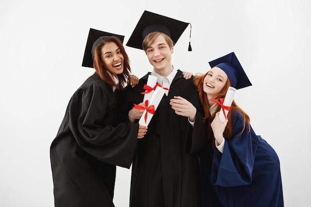 Szczęśliwi przyjaciele kończą studia uśmiecha się mienie dyplomy.