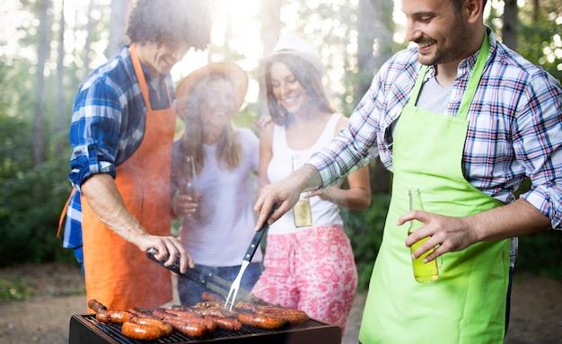 Szczęśliwi przyjaciele korzystający z grilla i imprezy grillowej na świeżym powietrzu