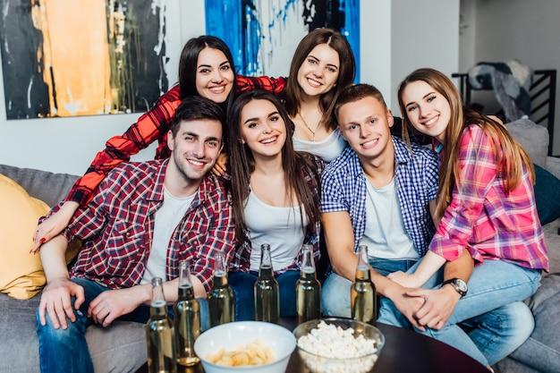 Szczęśliwi przyjaciele lub kibice oglądający piłkę nożną w telewizji i świętujący zwycięstwo w domu. jeść popcorn i pić piwo.