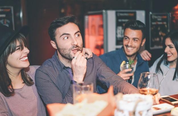 Szczęśliwi przyjaciele ma zabawę pije koktajl w barze