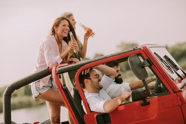 Szczęśliwi przyjaciele ma zabawę w kabrioletu samochodzie przy wakacje