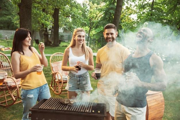 Szczęśliwi przyjaciele mają piwo i grilla w słoneczny dzień