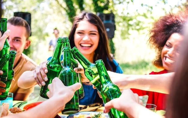 Szczęśliwi przyjaciele millenialsów bawią się na przyjęciu w ogrodzie z grillem - koncepcja stylu życia i przyjaźni z młodymi ludźmi opiekania butelkowanego piwa podczas letniego spotkania - ciepły, jasny filtr z naciskiem na butelki