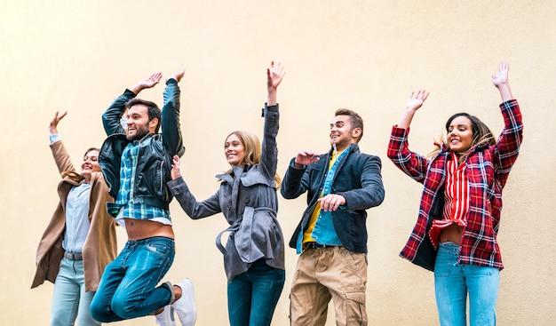 Szczęśliwi przyjaciele millennials skacze przeciw ściana z cegieł