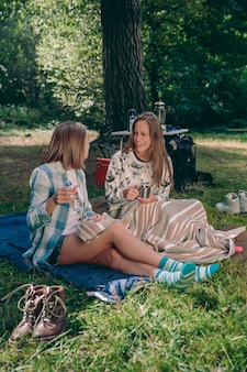 Szczęśliwi przyjaciele młodych kobiet śmieją się siedząc na kempingu w lesie
