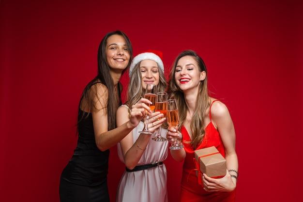 Szczęśliwi przyjaciele młodych kobiet z prezentem i szampanem razem świętuje wakacje na imprezie na czerwonej ścianie, miejsce