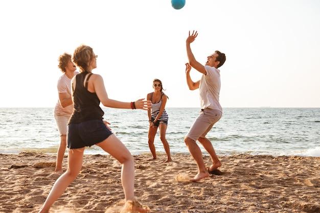 Szczęśliwi przyjaciele na świeżym powietrzu na plaży grać w siatkówkę, zabawy
