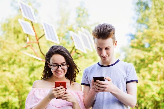 Szczęśliwi przyjaciele naładowali swoje telefony komórkowe za pomocą nowoczesnych paneli słonecznych stojących w parku i wykorzystują zalety energii odnawialnej