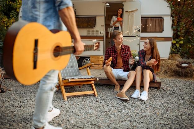 Szczęśliwi przyjaciele, odpoczynek z gitarą na pikniku na kempingu w lesie. młodzież przeżywa letnią przygodę na kamperze, samochodzie kempingowym dwie pary odpoczywa, podróżuje z przyczepą