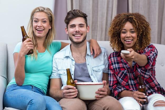 Szczęśliwi przyjaciele ogląda mecz piłkarskiego podczas gdy siedzący na kanapie