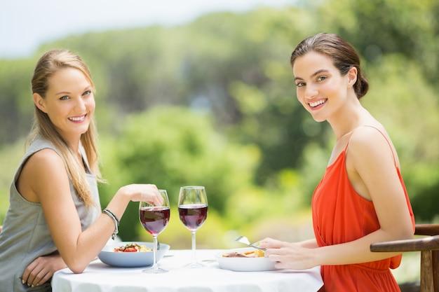 Szczęśliwi przyjaciele ono uśmiecha się podczas gdy mieć jedzenie w restauraci