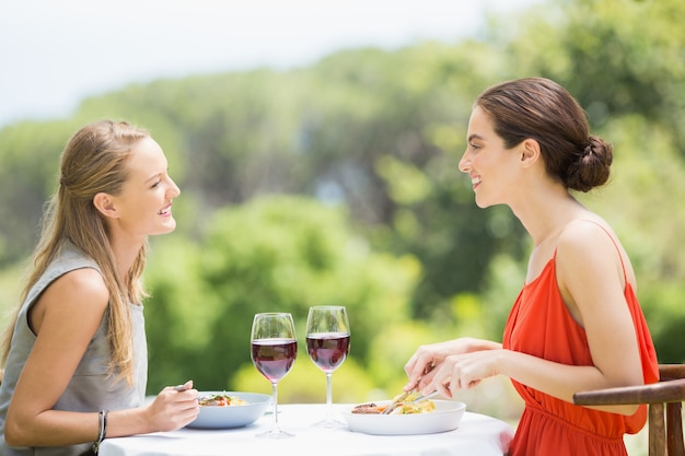 Szczęśliwi przyjaciele ono uśmiecha się podczas gdy mieć jedzenie