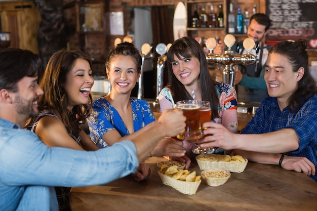 Szczęśliwi przyjaciele opiekania szklanek piwa