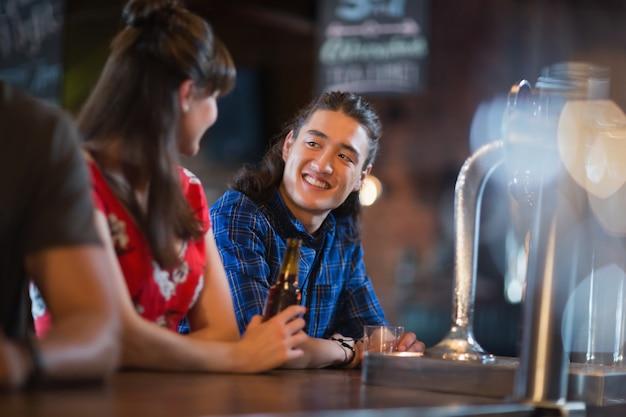 Szczęśliwi przyjaciele patrząc na siebie, opierając się na blacie barowym
