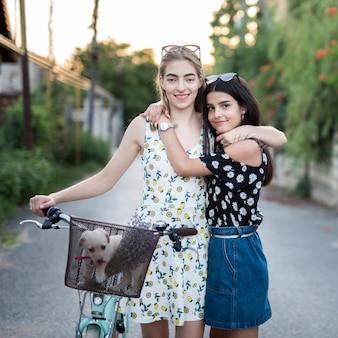 Szczęśliwi przyjaciele patrzeje kamerę z bicyklem