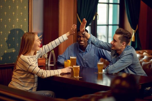 Szczęśliwi przyjaciele piją alkohol i bawią się przy stole w barze