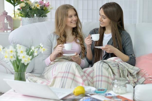 Szczęśliwi przyjaciele piją kawę lub herbatę na kanapie w domu
