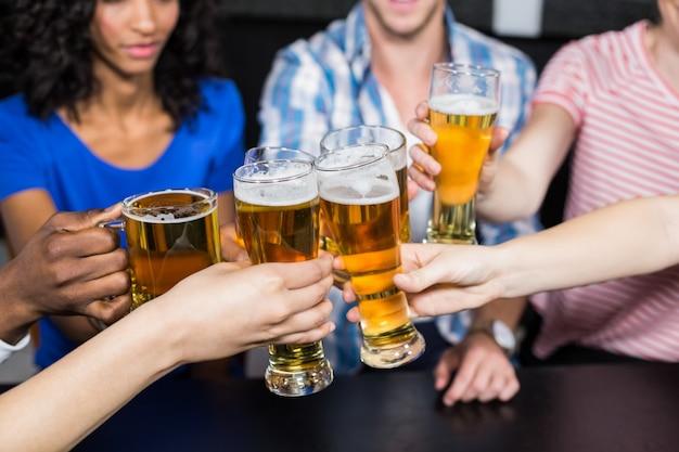 Szczęśliwi przyjaciele pije piwo i opiekają