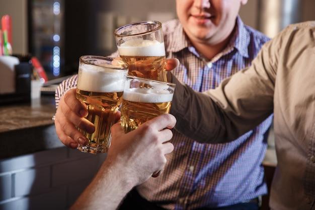 Szczęśliwi przyjaciele pije piwo przy kontuarem w pubie