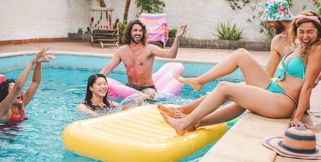 Szczęśliwi przyjaciele pluskający wodę na imprezie przy basenie w wynajętej willi - młodzi ludzie świetnie się bawią na wakacjach