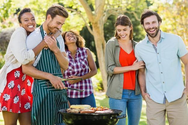 Szczęśliwi przyjaciele przygotowywa grilla grilla w parku